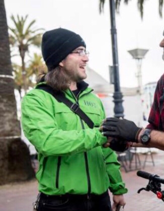 A man in a lime green jacket shakes hands with someone (the person is cut off from the rest of the photo)